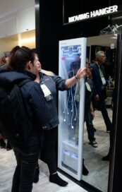 Two women look at and try out a display of LG's Moving Hanger technology at the LG Styler display zone.