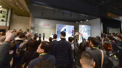 Far shot of a demonstration session for LG's CLOi commercial robots with attendees watching a presentation at the company's CES 2019 booth