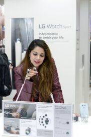 A woman tries out a sample of the LG Watch Sport smart watch at LG's MWC 2017 booth.