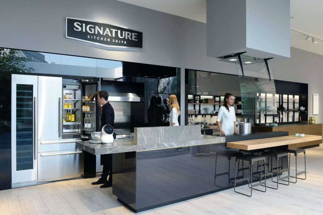 Another view of the LG Signature Kitchen Suite display zone, three models are standing in the kitchen.