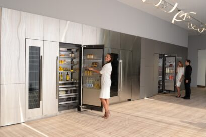 A close view of a refrigerator in the LG Signature Kitchen Suite display zone, a model is opening the fridge door.