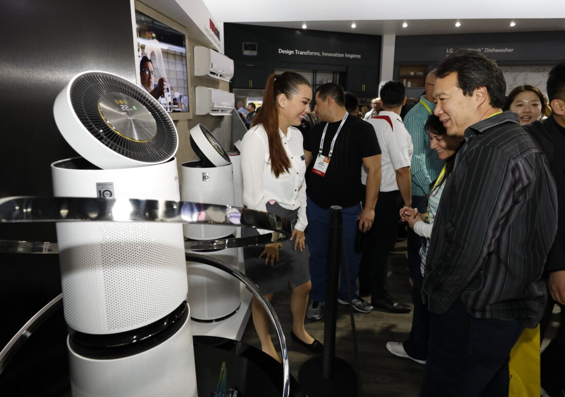 A female attendant stands next to the LG PuriCare Air Purifier talking to conference attendees in the LG display zone at CES 2017.