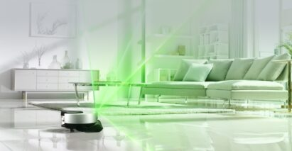 A promotional image of LG CordZeroThinQ beaming green light over the living room as it scans the room