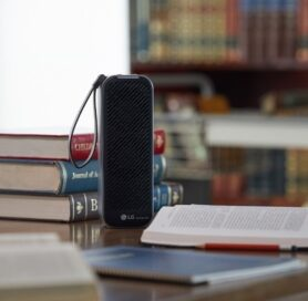 The front view of LG PuriCare Mini Air Purifier surrounded by books