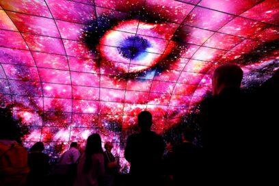 Visitors stand underneath LG OLED Tunnel and look up the screens.