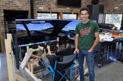 Rick Kelly poses and in front of his new racing simulator as his son uses it behind him