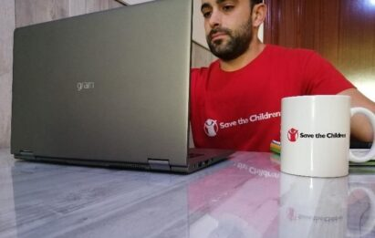 A man using the LG gram next to a mug displaying the Save the Children organization logo