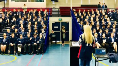 Melissa McGuinness stands in front of school children during assembly to talk to them about road safety