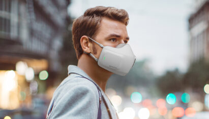 A man on a street wearing LG PuriCare wearable Air Purifier