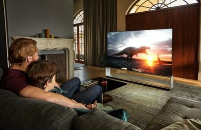 A father and son watch a movie on LG's OLED TV which provides a true cinematic experience