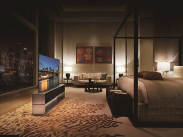 Left-side view of LG SIGNATURE OLED R inside a modern bedroom in Full View mode, its on-screen image blending into the night skyline seen from the large window behind