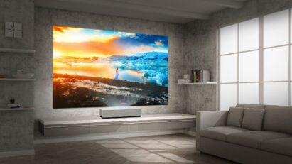 LG CineBeam stands closely to the wall of a modern living room yet still projects a large high-res image of a majestic glacier during a sunset