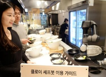 A man and women at a buffet being served their meals by LG ChefBot