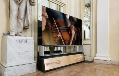 The LG SIGNATURE OLED 8K TV standing next to a statue of Giuseppe Verdi in La Scala displays a musician playing the violin during Rigoletto