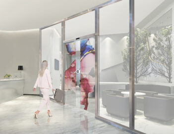 A woman walking through an office's transparent OLED automatic door which is displaying flowers with a welcoming message