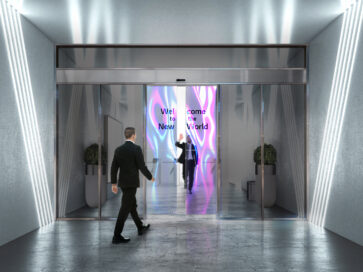 A man greeting a visitor through an opening transparent OLED automatic door, which is displaying the colorful words, 'Welcome to the New World'