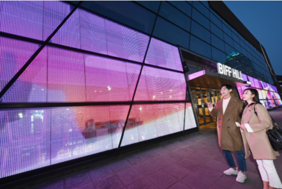 A man and a woman marveling at the LG Transparent LED Film being displayed on the façade of the Busan Cinema Center.